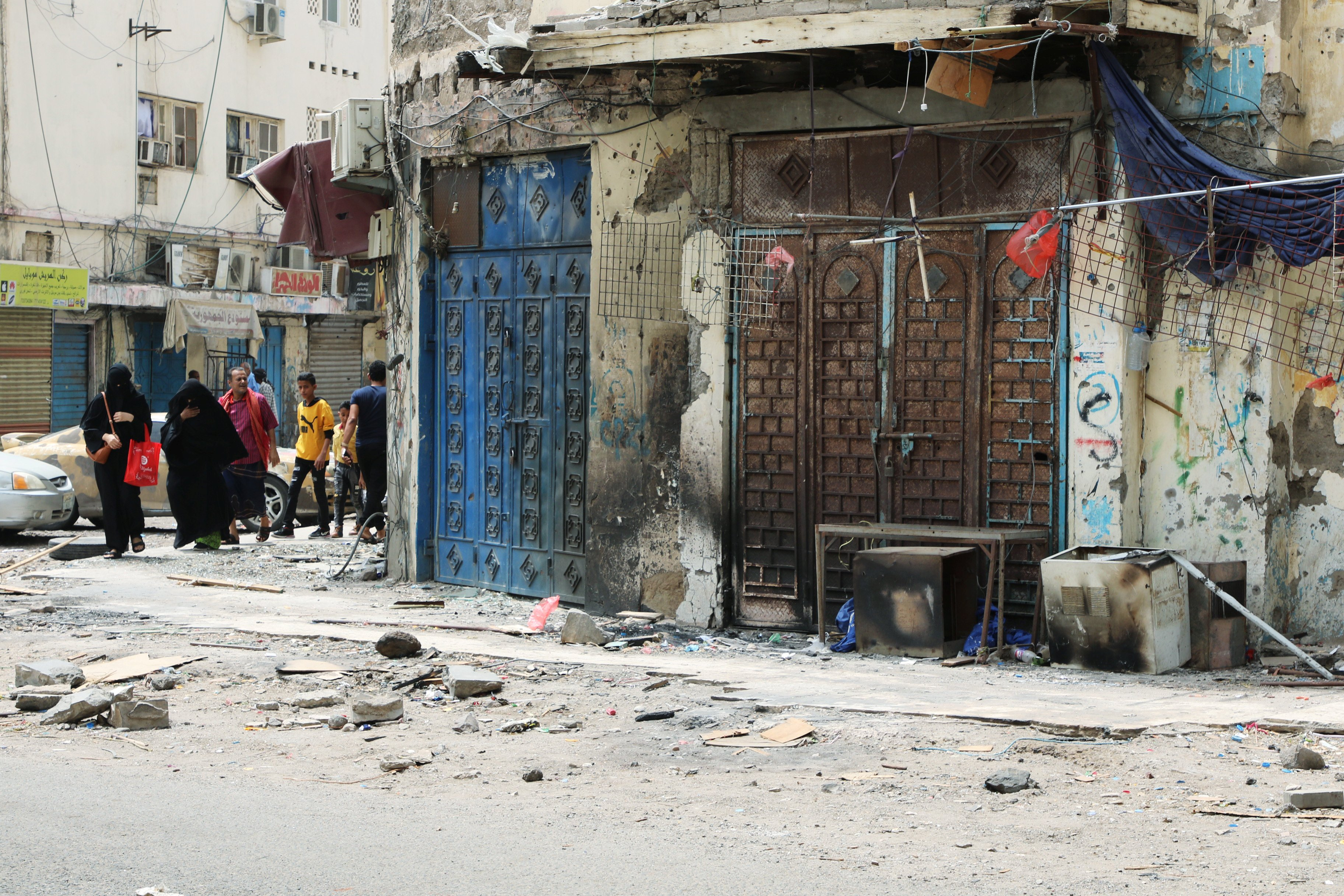 Yemenis walk past shops damaged during clashes in Aden (Reuters)