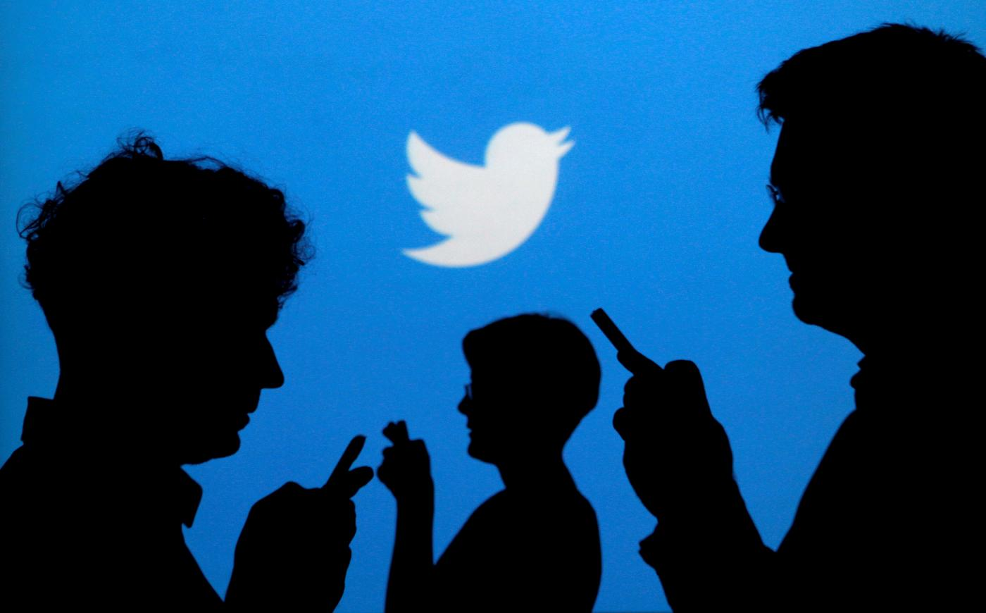 People hold mobile phones against a backdrop projected with the Twitter logo (Reuters)