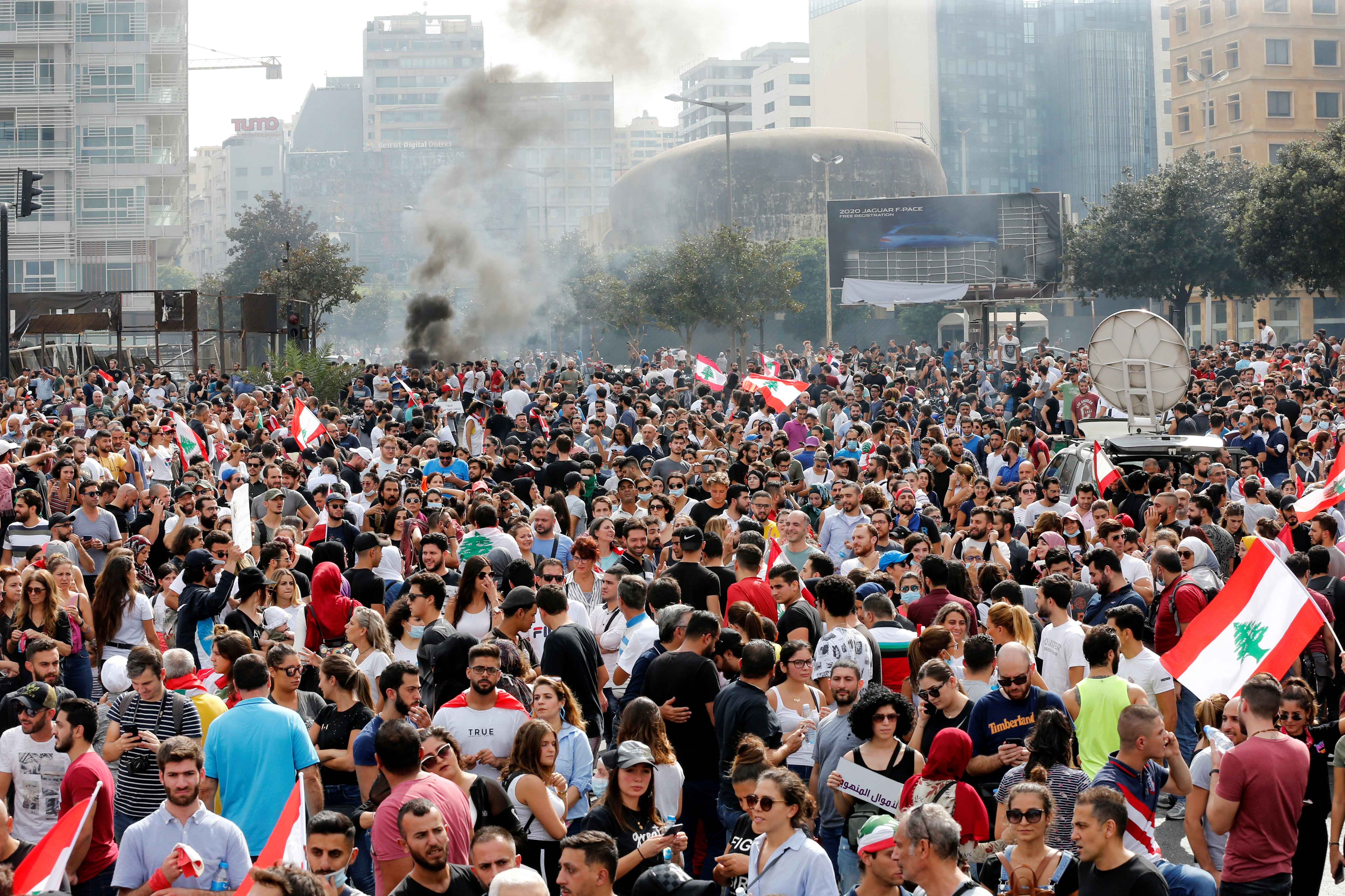 Smoke rises as demonstrators gather during a protest in Beirut over deteriorating economic situation on 18 October (Reuters)