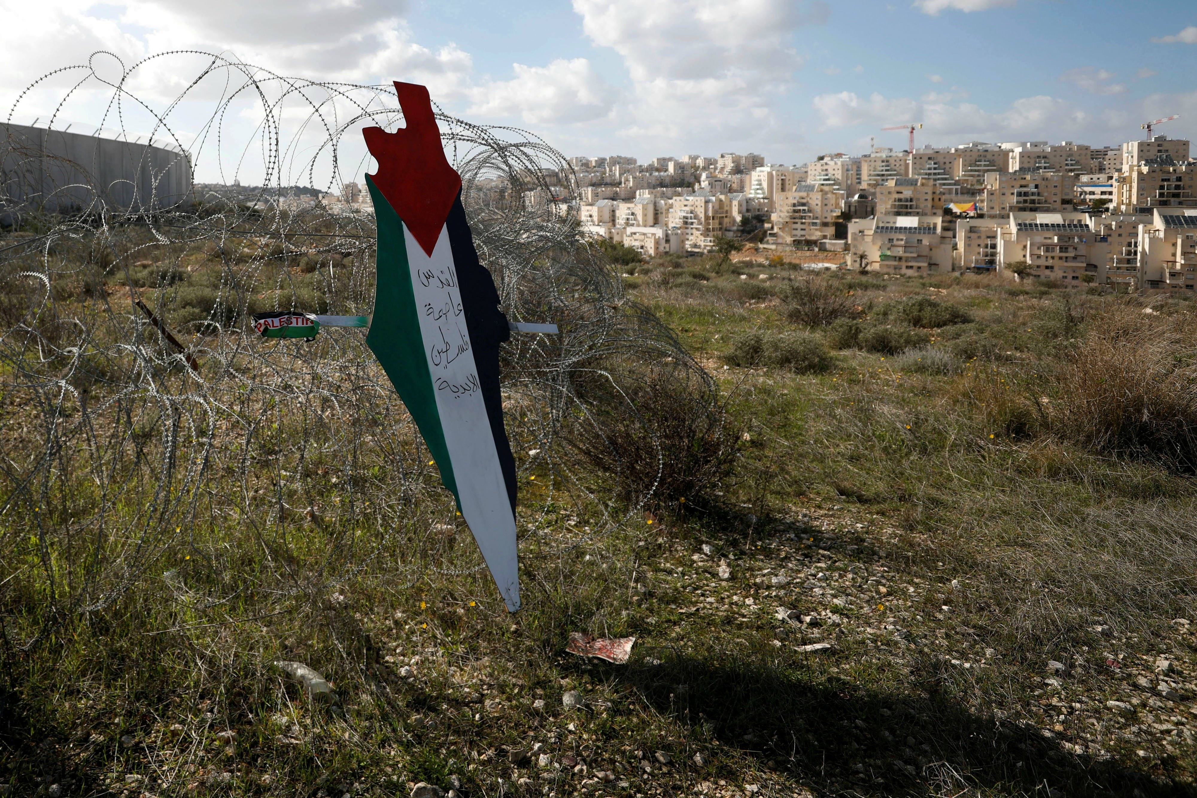 A map with the colours of the Palestinian flag reading 'Jerusalem is the eternal capital of Palestine' is seen near a Jewish settlement in the occupied West Bank (Reuters)