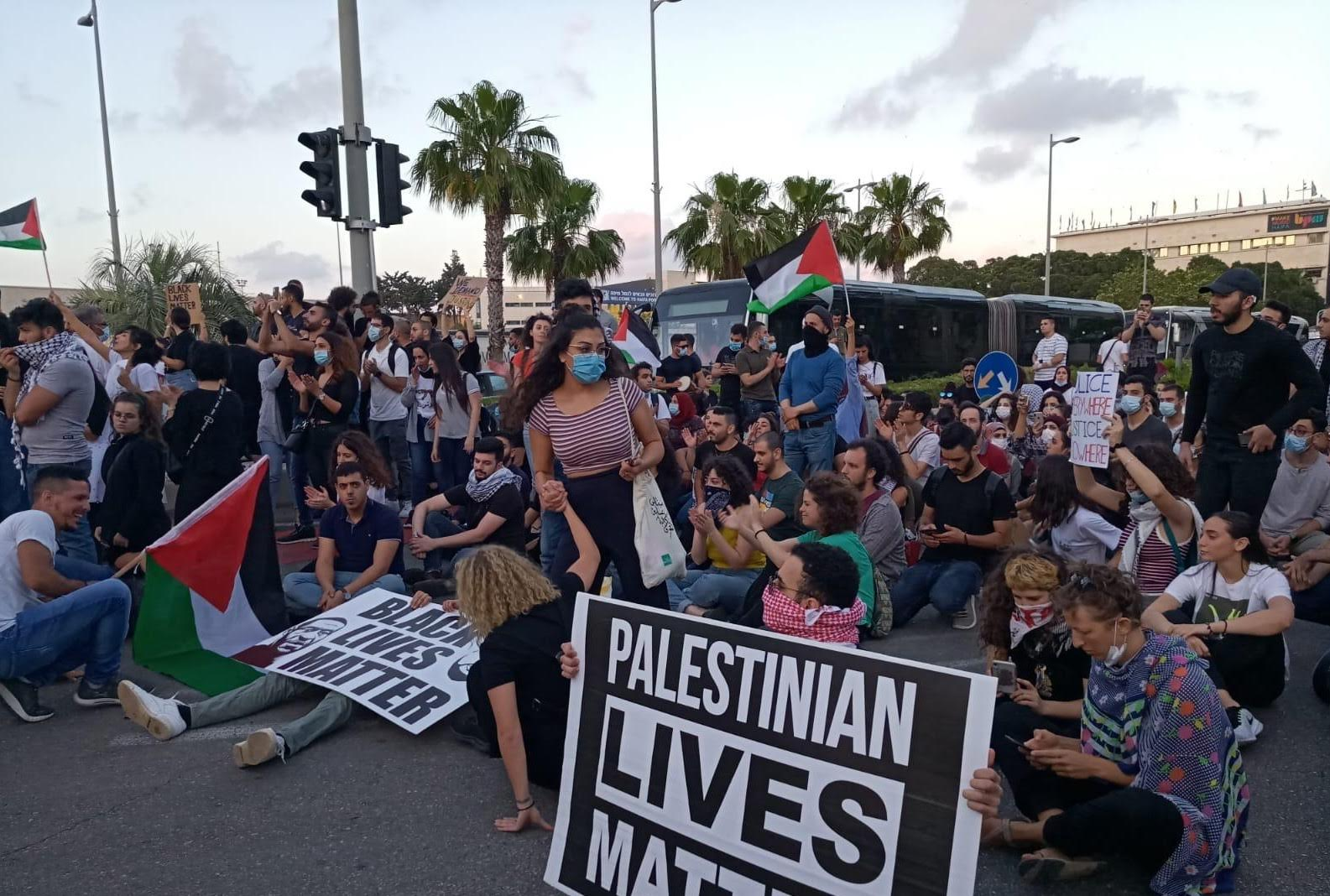 "Protesters hold ""Black Lives Matter"" and ""Palestinian Lives Matter"" signs in Haifa, Israel, in June 2020 (MEE/Mohamad Kadan)"