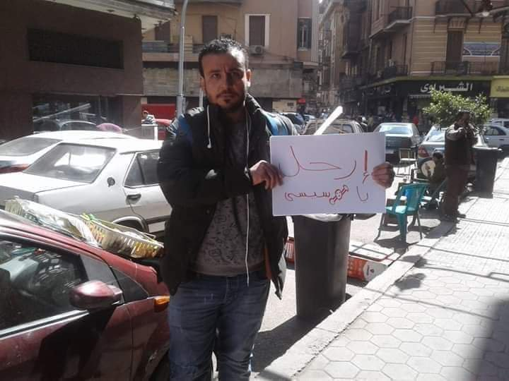 "Ahmed Mohy holds a sign reading ""Step down Sisi"" before being arrested (Social media)"