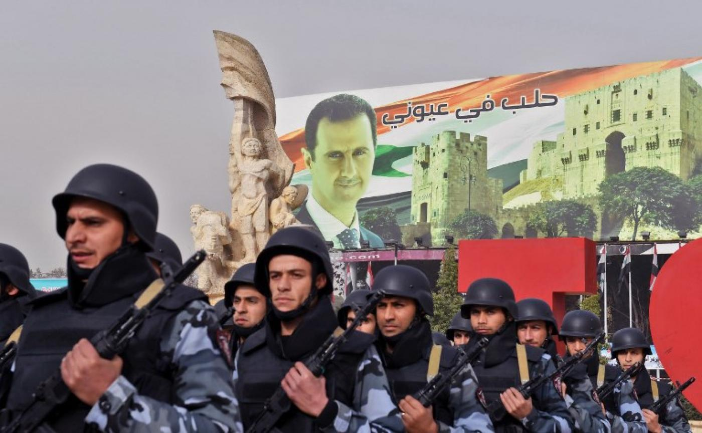 Syrian soldiers posing in front of a portrait of Syrian president (AFP)