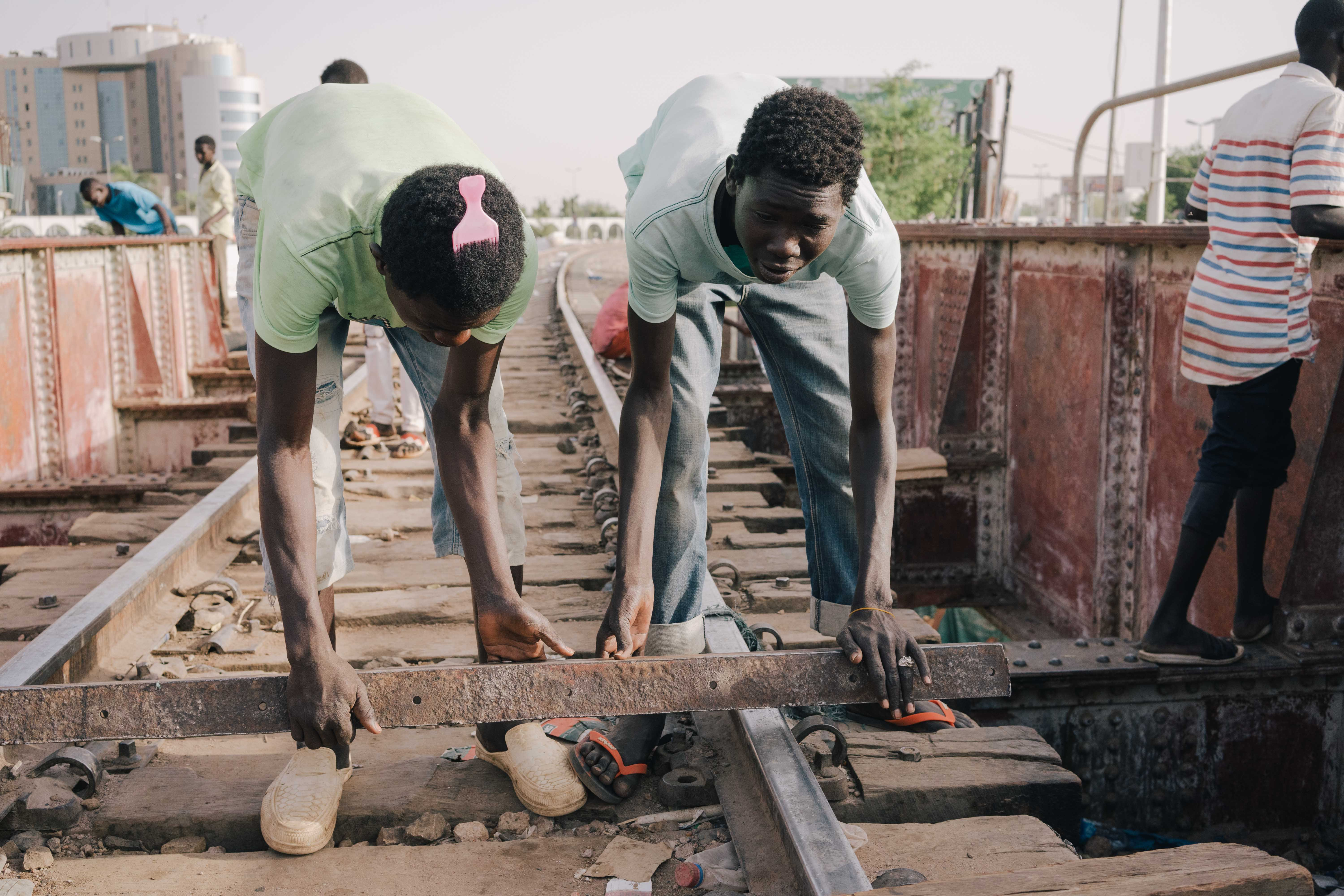 Sudanese youths beat a rhythm on a metal railway bridge in Khartoum (MEE/Kaamil Ahmed)