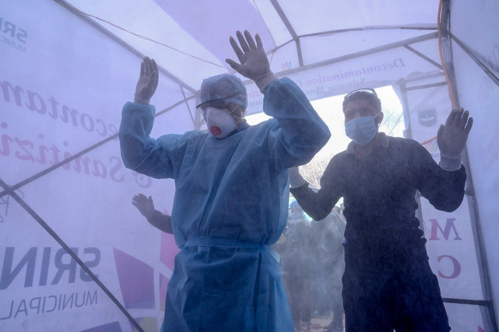 Medical staff walk through a disinfecting tunnel before entering a hospital in Srinagar on 2 April (AFP)