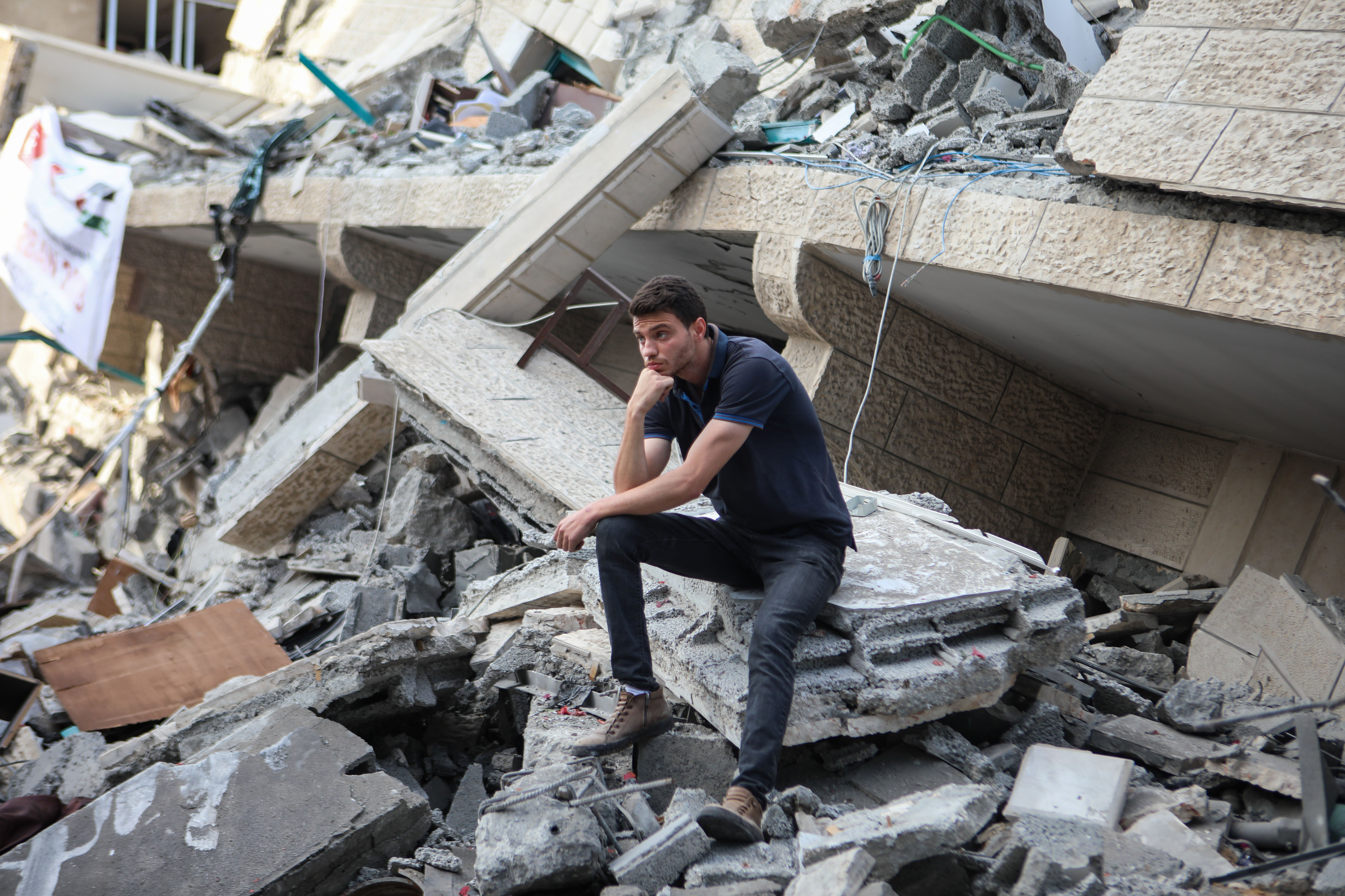A Palestinian sits on the rubble of a building destroyed by an Israeli air strike in Gaza (MEE/Mohammed al-Hajjar)