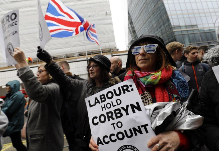 Demonstrators gather outside Labour Party offices in London on 8 April 2018 (AFP)