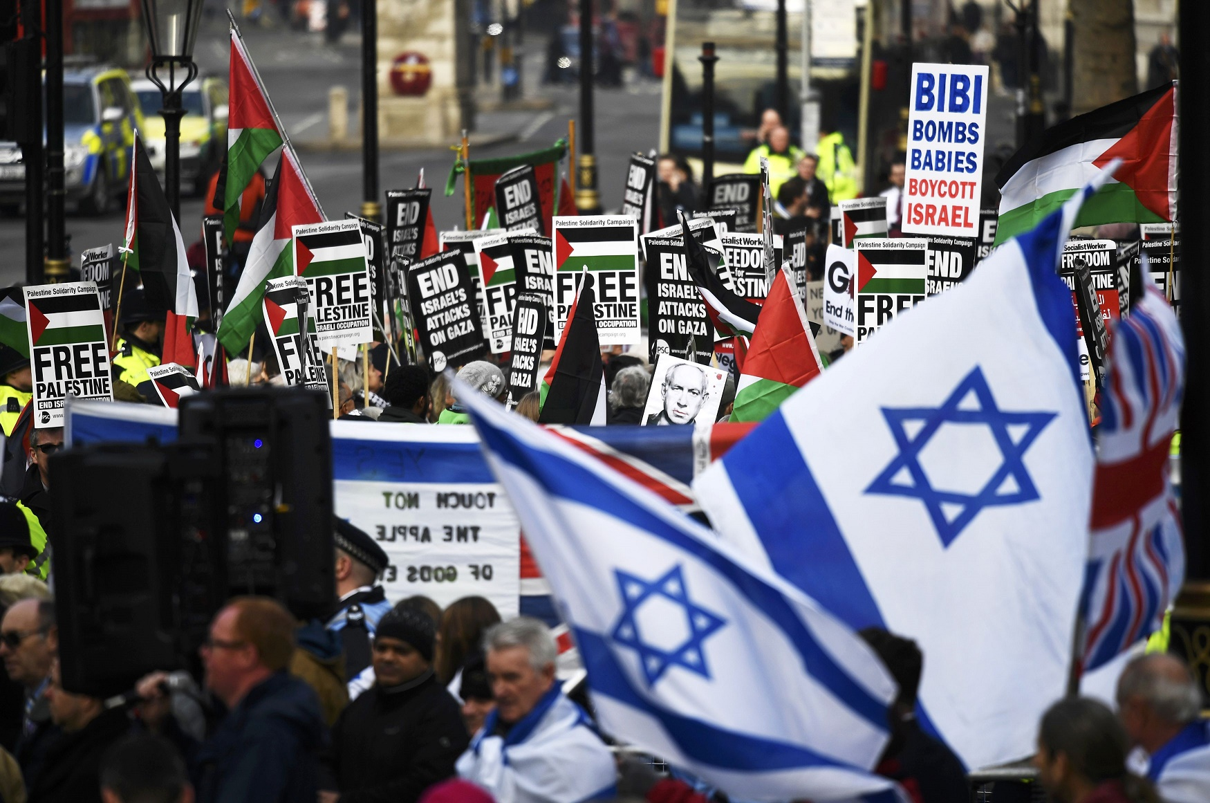 Pro-Palestinian protesters are flanked by supporters of Israel at protests near 10 Downing Street (Reuters)