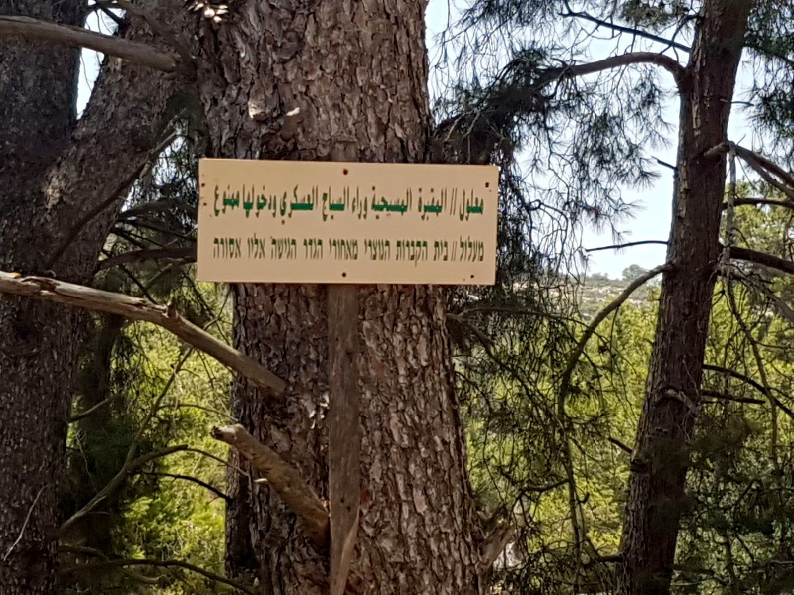 A Hebrew and Arabic sign in Ma'alul on the edge of the Israeli military base thst reads: Maalul | Christian cemetery behind the fence. Entry is forbidden