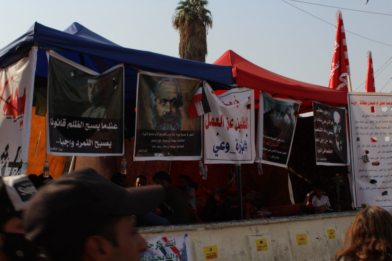 Posters depict Karl Marx, Rosa Luxemburg and other leftist figures in Tahrir Square (MEE/Alex MacDonald)