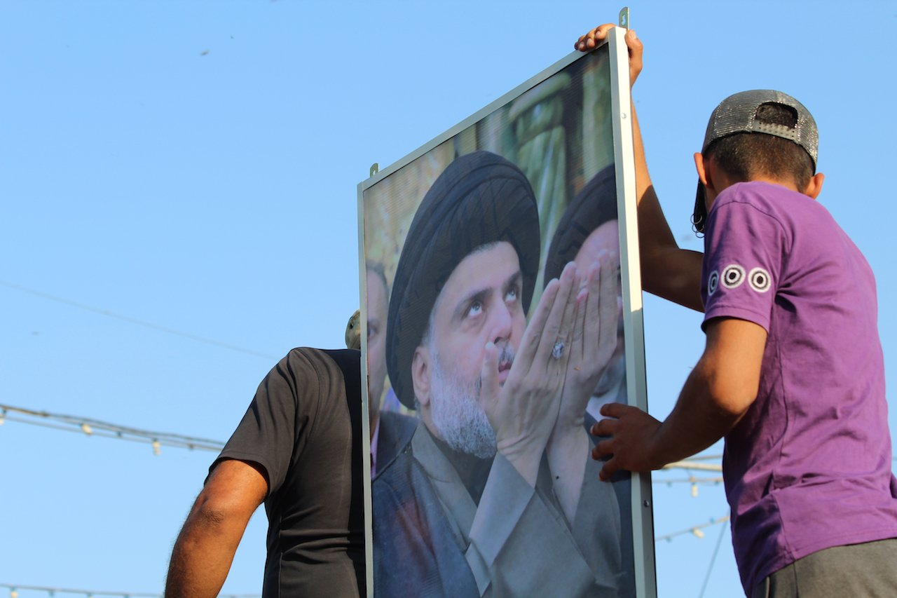Protesters hold up a portrait of Muqtada al-Sadr in the centre of Tahrir square (MEE/Alex MacDonald)