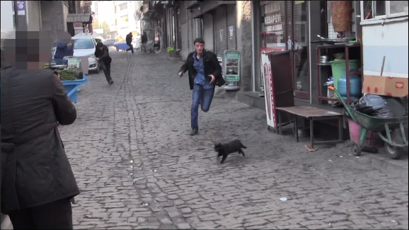 A still shows a suspected PKK militant running down a street being targeted by police (screenshot)
