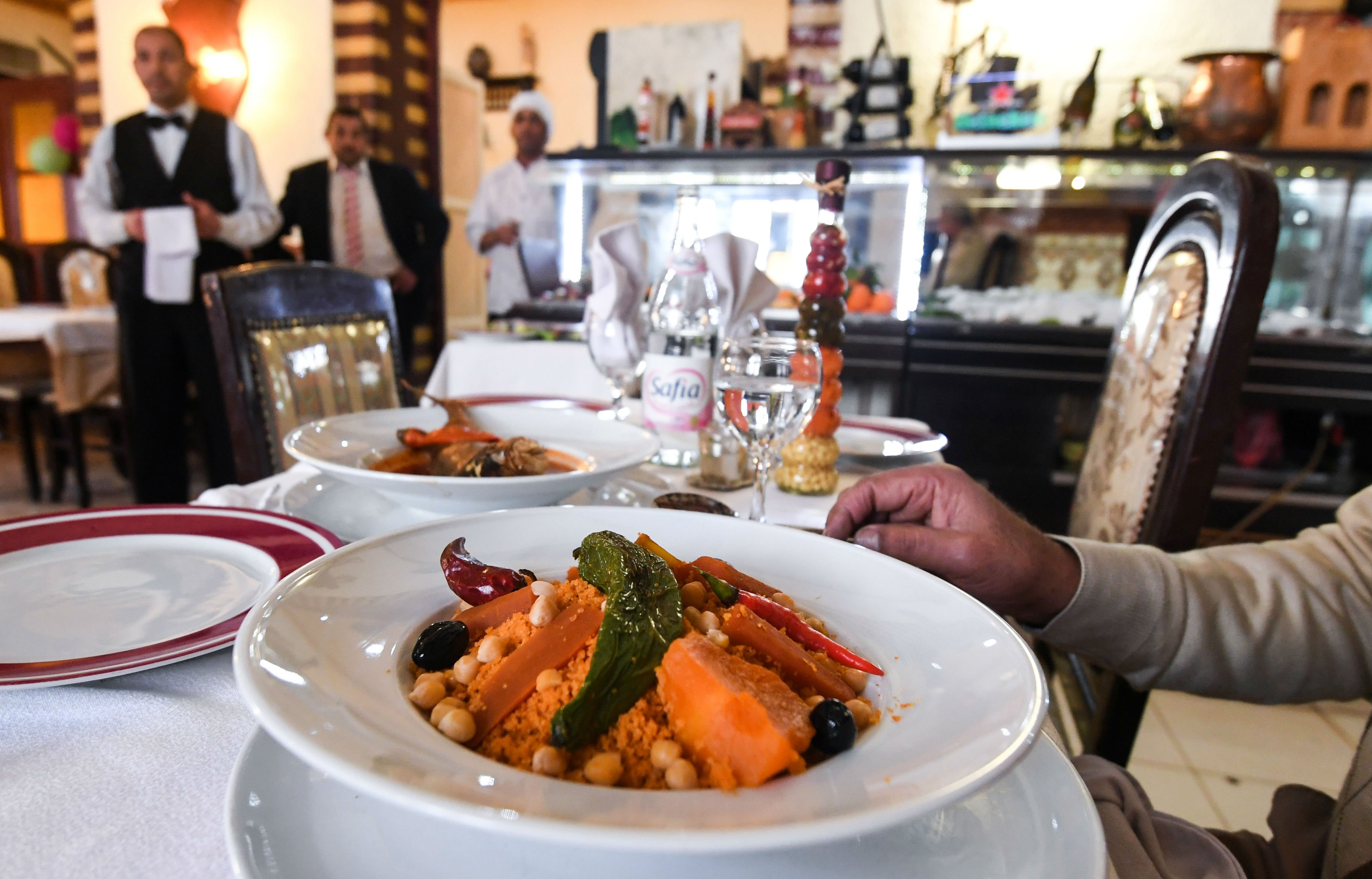 Patrons are served couscous dish at the restaurant L'Orient in Tunis in January 2018 (AFP)