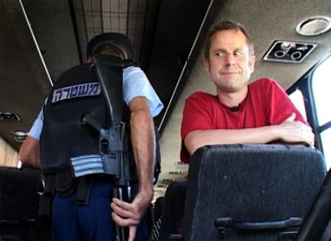 Jeremy Hardy on a coach being searched by Israeli police (screenshot)