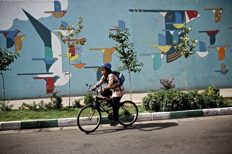 An Iranian woman rides her bicycle in a southwestern street of Tehran on June 29, 2015
