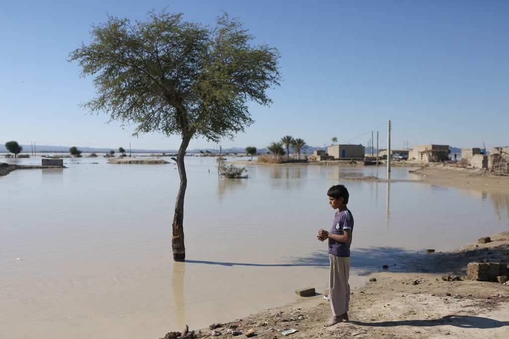 An Iranian youth stands in front of a flooded area in Dashtiari village in Iran's Sistan and Baluchistan region