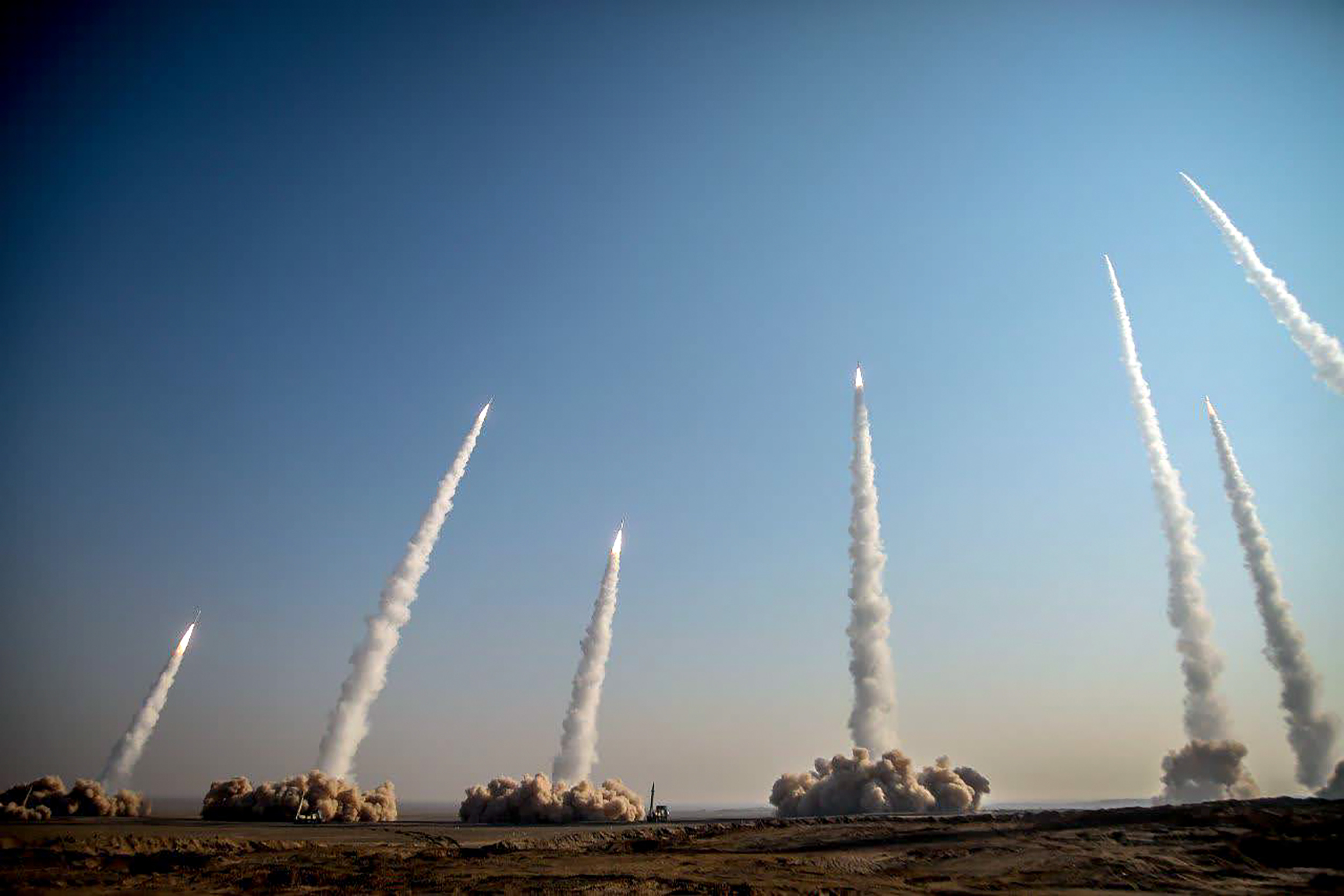 Several missiles are seen being being launched in a desert area in Iran on Friday (AFP)