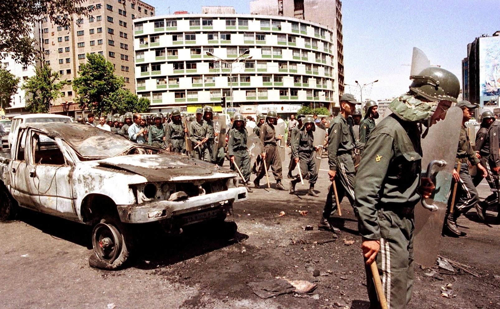 Iranian anti-riot police pass by a destroyed car in the centre of Tehran on 12 July 1999 (AFP)