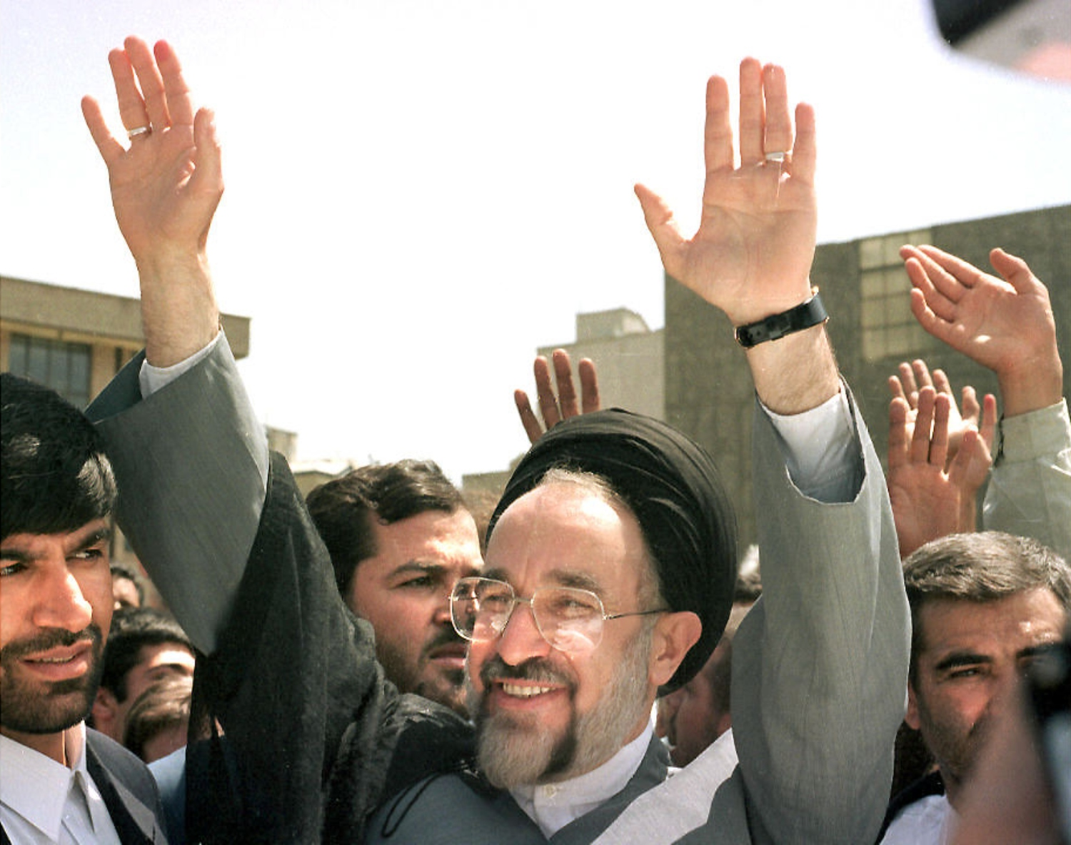 Reformist presidential candidate Mohammed Khatami waves at a crowd of supporters outside of a polling station on 23 May 1997 (AFP)