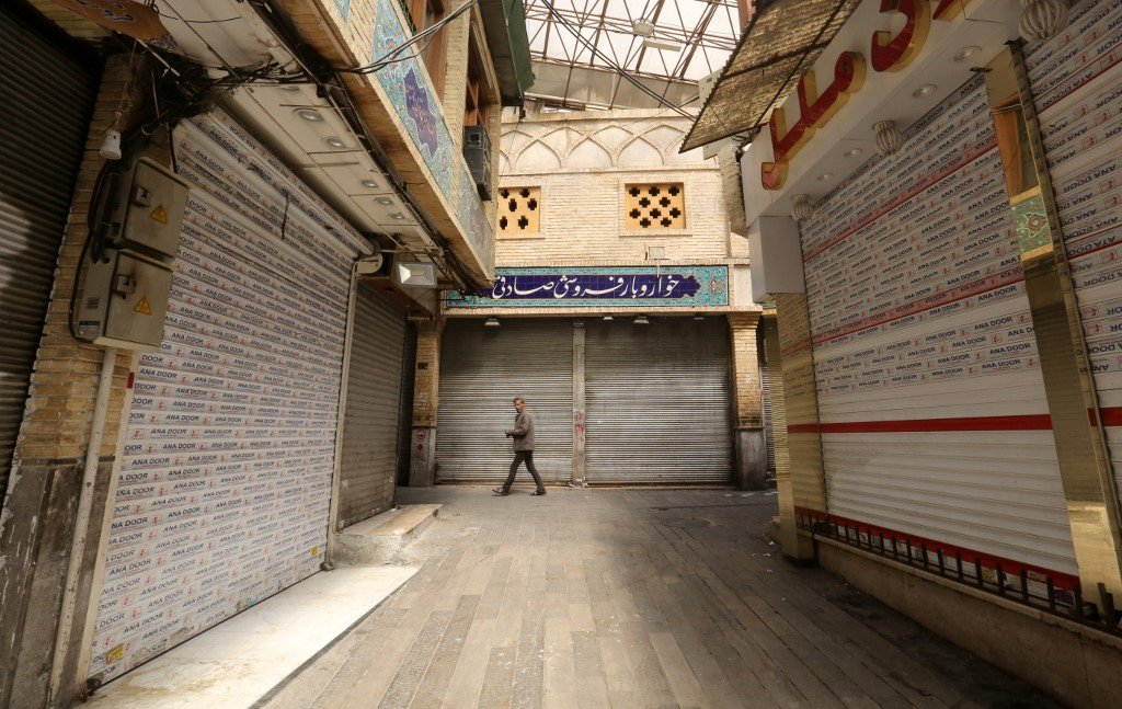 A lone Iranian man walks through a closed indoor market in Tehran on 5 April (AFP)