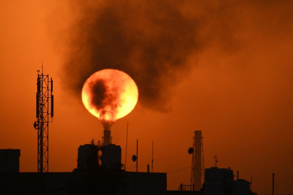 The sun sets over an oil refinery in southern Iraq on 8 March 2021 (AFP)