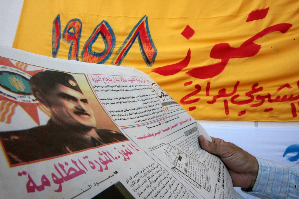 An Iraqi reads the communist party newspaper, 14 July 2007 in Baghdad, bearing a front page picture of General Abd al-Karim Qassim during a ceremony to commemorate the 1958 coup.