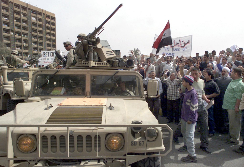 Iraqi protesters shout anti-US slogans as they surround military vehicles in 2003 in Baghdad (AFP)