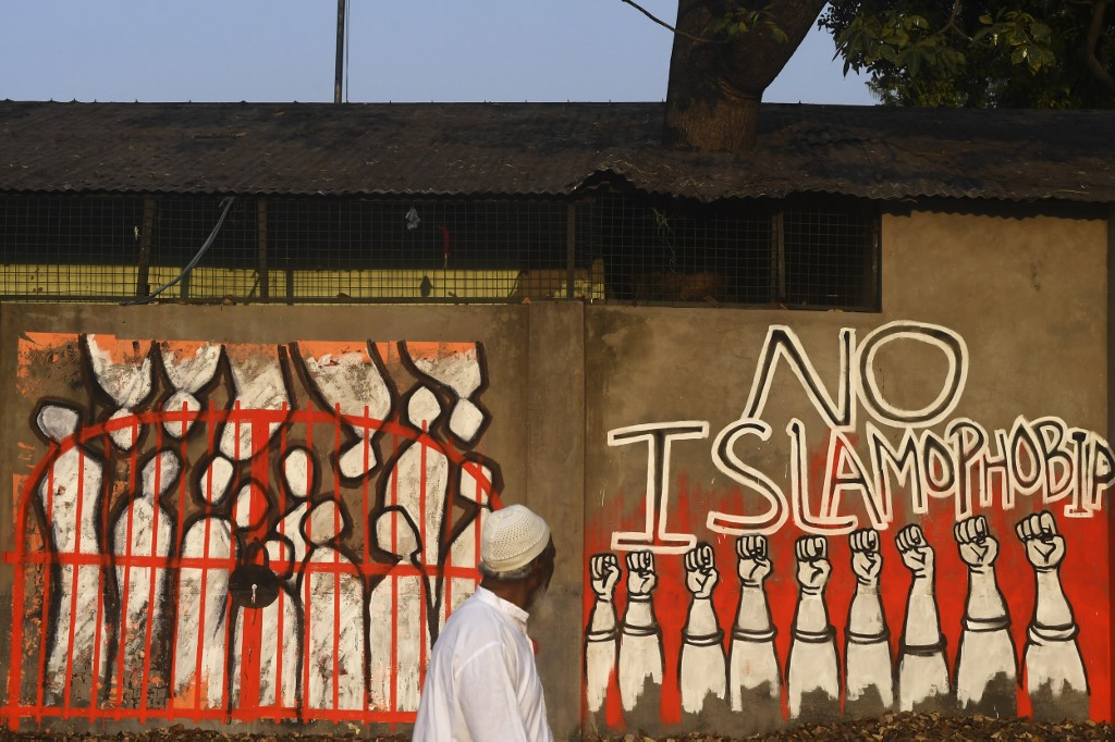 A man walks by a wall protesting Islamophobia in Kolkata, India, on 14 February (AFP)