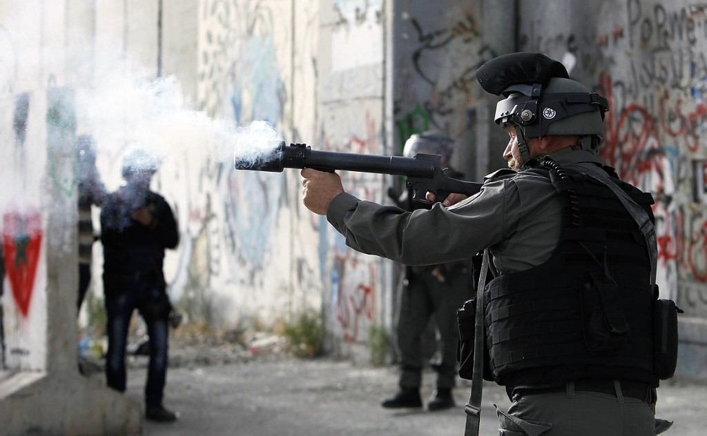An Israeli border guard fires tear gas towards Palestinians in Bethlehem in 2017 (AFP)