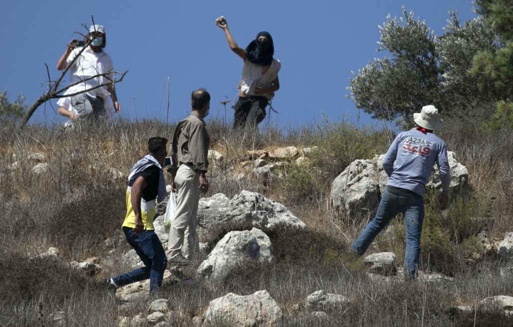 Israeli settlers attack Palestinian farmers near the Yitzhar settlement on 7 October (AFP)