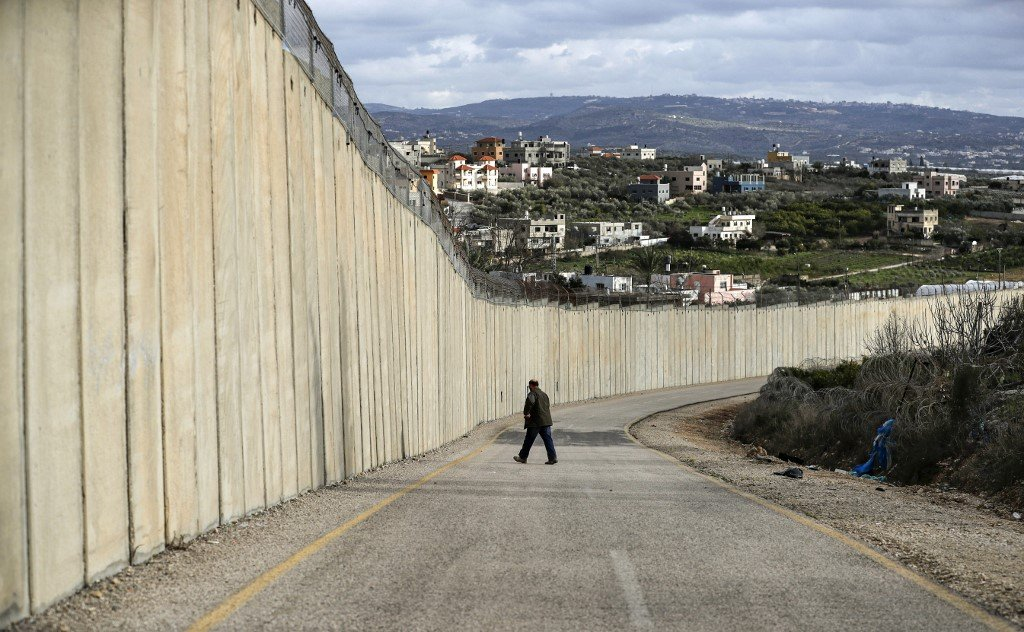 A man walks by Israel's separation wall on 1 February (AFP)