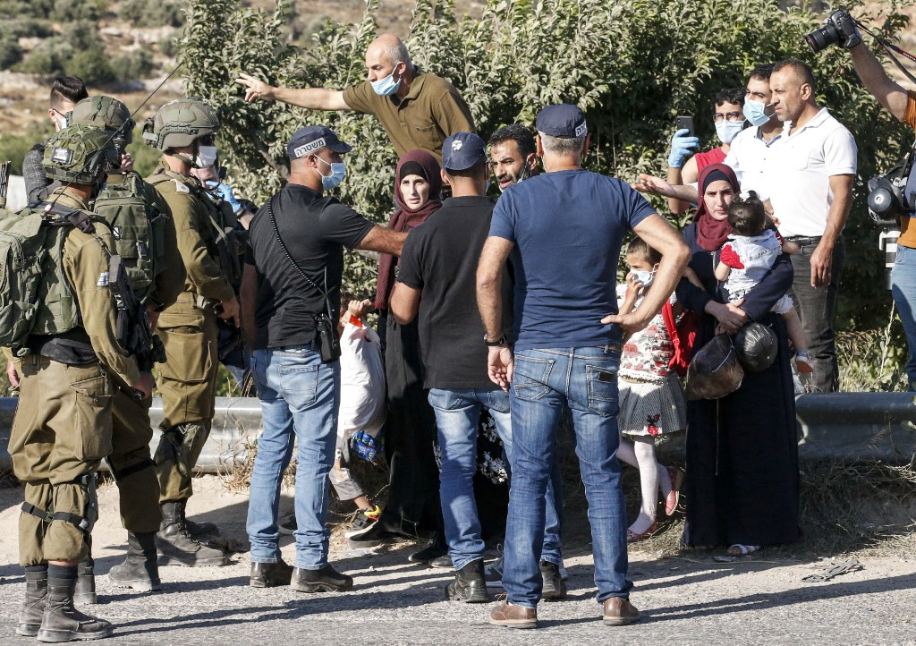 Palestinians are blocked by Israeli policemen and army soldiers, some clad in masks due to the COVID-19 coronavirus pandemic, while on their way home at the entrance of a junction by the Palestinian village of Halhul, north of Hebron