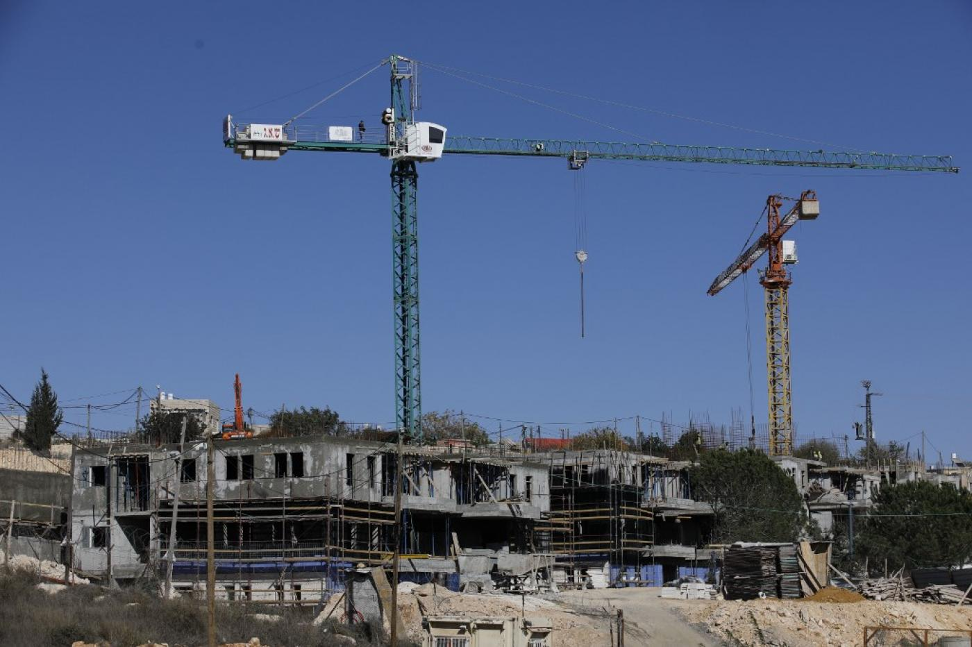 .Construction takes place at an illegal Israeli settlement near Bethlehem on 19 November (AFP)