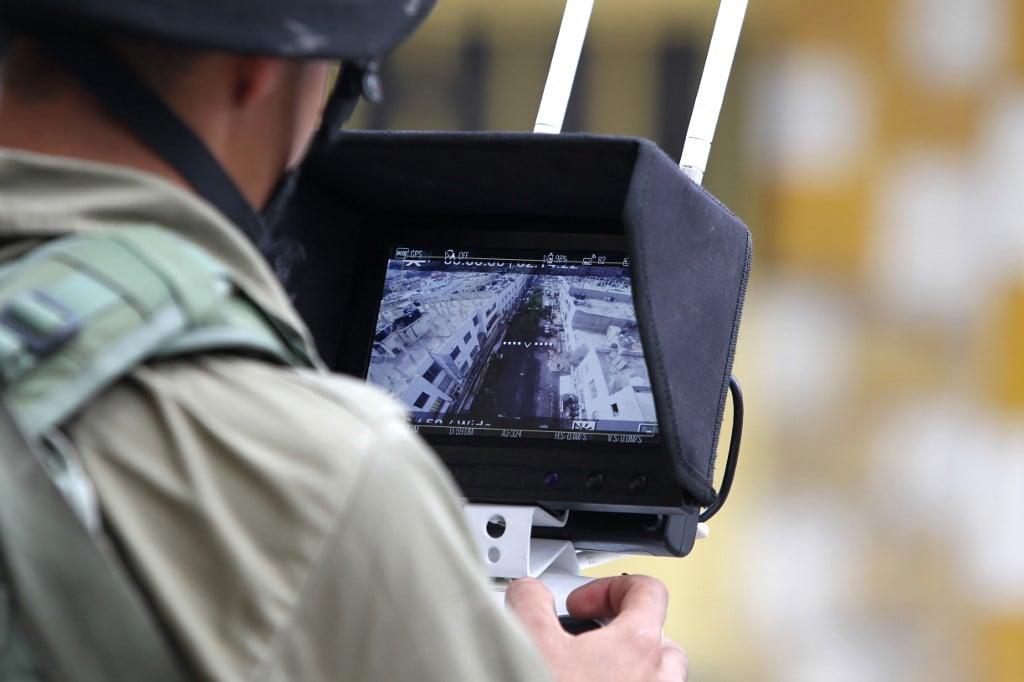 Un soldat israélien utilise un drone pour surveiller la population palestinienne dans la ville d'Hébron, en Cisjordanie occupée, en 2015 (AFP)