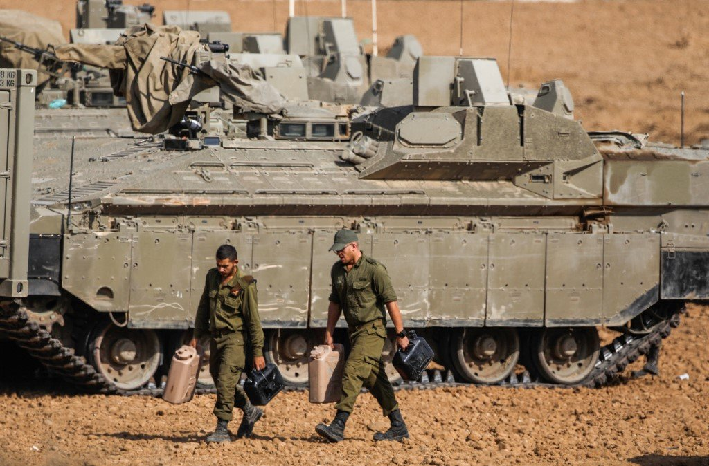 Israeli soldiers walk next to armoured vehicles near Gaza on 13 November (AFP)