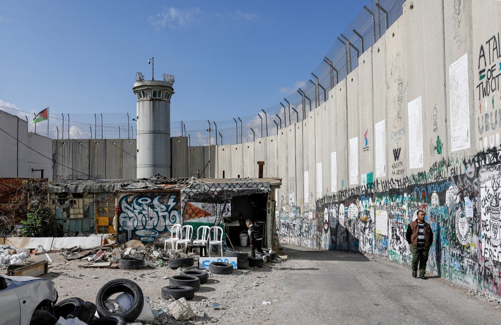 A man walks along Israel's separation wall in Bethlehem on 7 December (AFP)