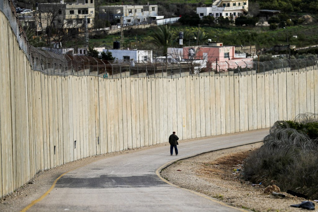 A man walks by Israel's separation wall in the occupied West Bank on 1 February (AFP)