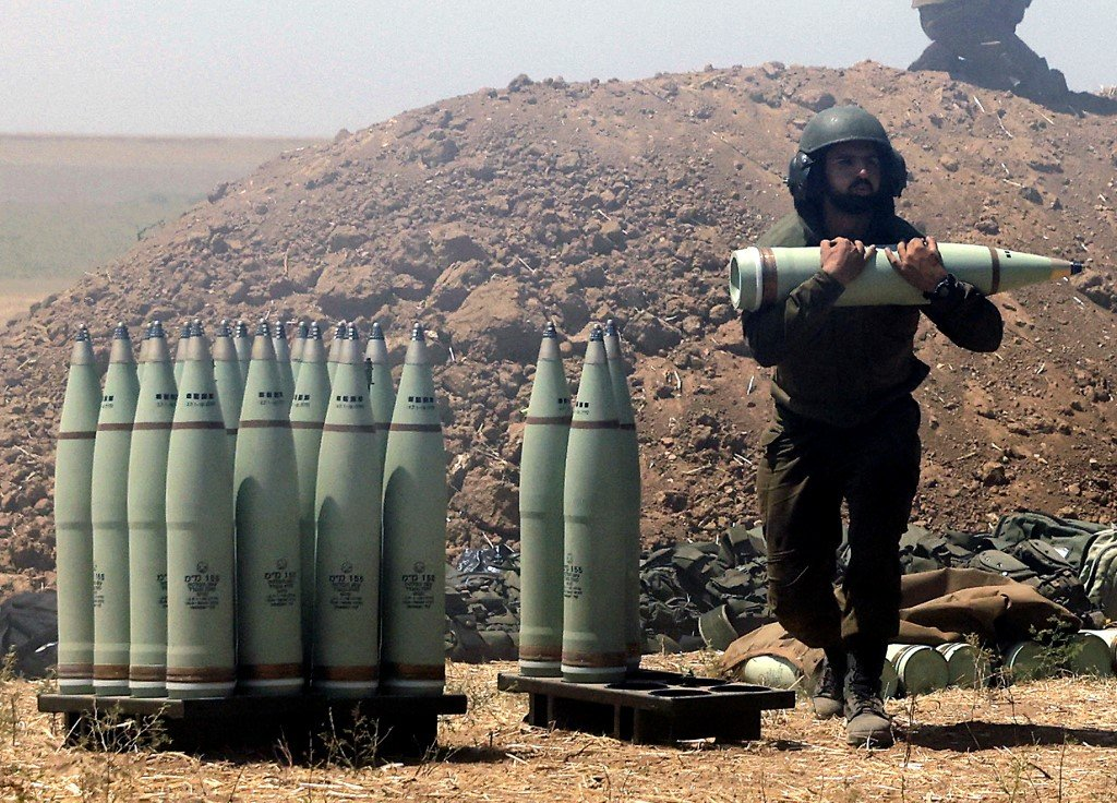 An Israeli soldier carries artillery shells to be fired towards Gaza on 19 May 2021 (AFP)
