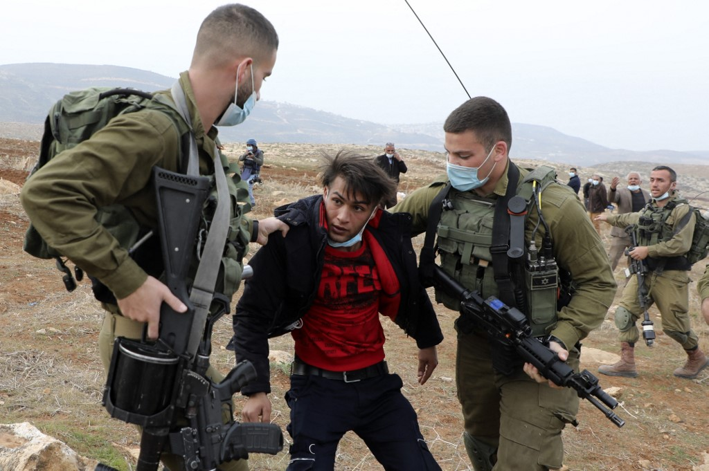 Israeli soldiers detain a Palestinian man during a protest against the seizure of Palestinian farmland by Jewish settlers in the occupied West Bank on 13 January 2021 (AFP)