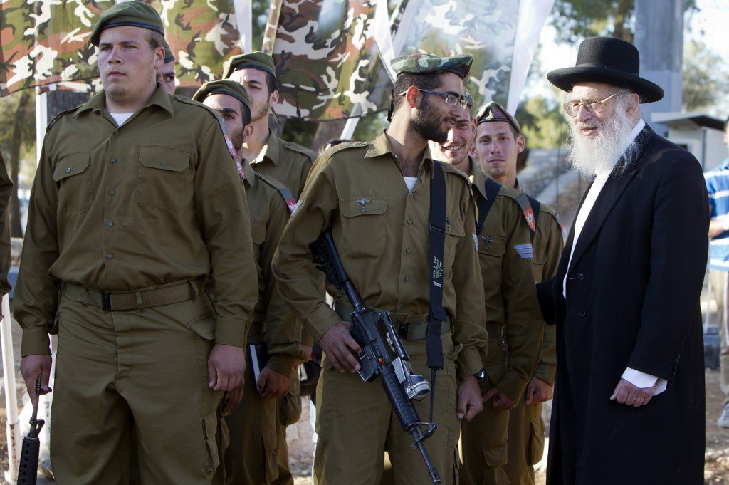 A rabbi speaks to a soldier with the Ultra-Orthodox 'Netzah Yehuda' Israeli army battalion at a swearing-in ceremony in Jerusalem (AFP)