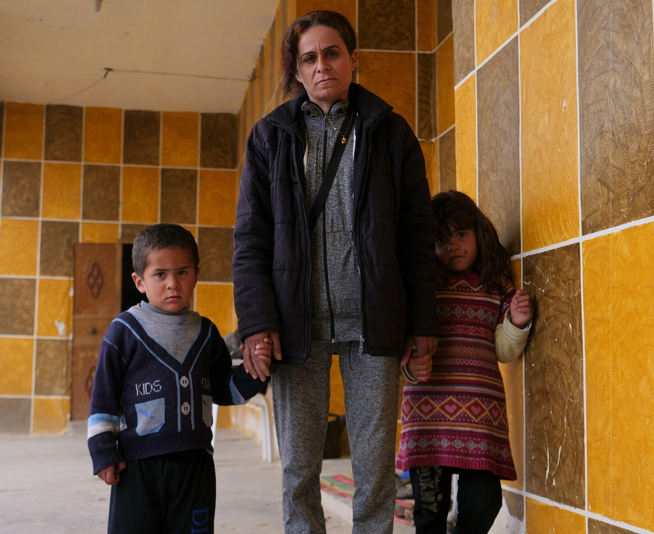 Jane, seen with her two children Ahmed and Farida, says the Yazidis didn't dare to declare their true identity when they arrived at the al-Hol camp (MEE/Ines Daif)