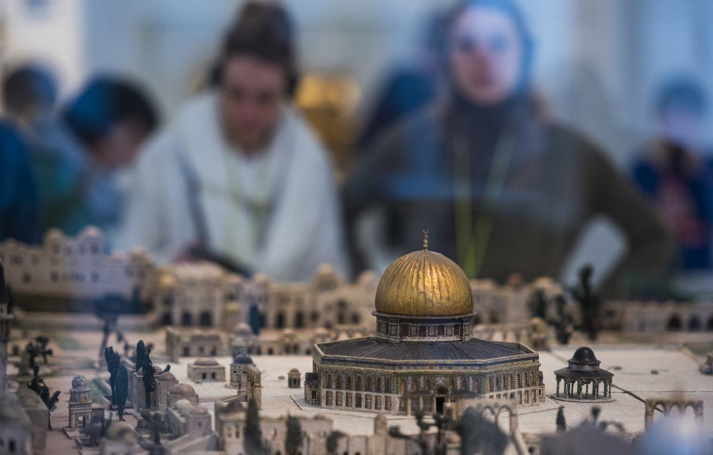 Visitors look at a model Dome of the Rock at the Jewish Museum in Berlin in 2017 (AFP)