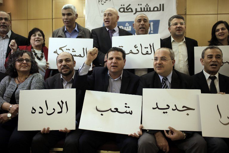 Israeli Arab political leaders hold placards urging voters to endorse the Joint List and usher in 'a new tomorrow' ahead of the 2015 elections (AFP)