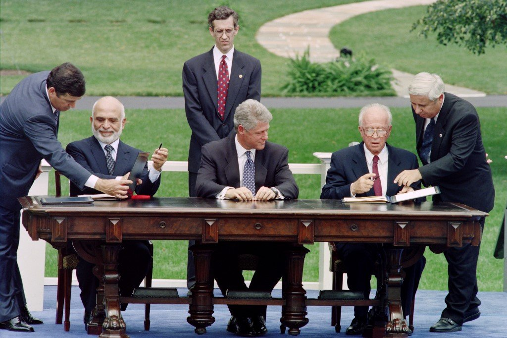 Israeli Prime Minister Yitzhak Rabin and Jordan's King Hussein sign the 1994 peace treaty in Washington as US President Bill Clinton looks on (AFP)
