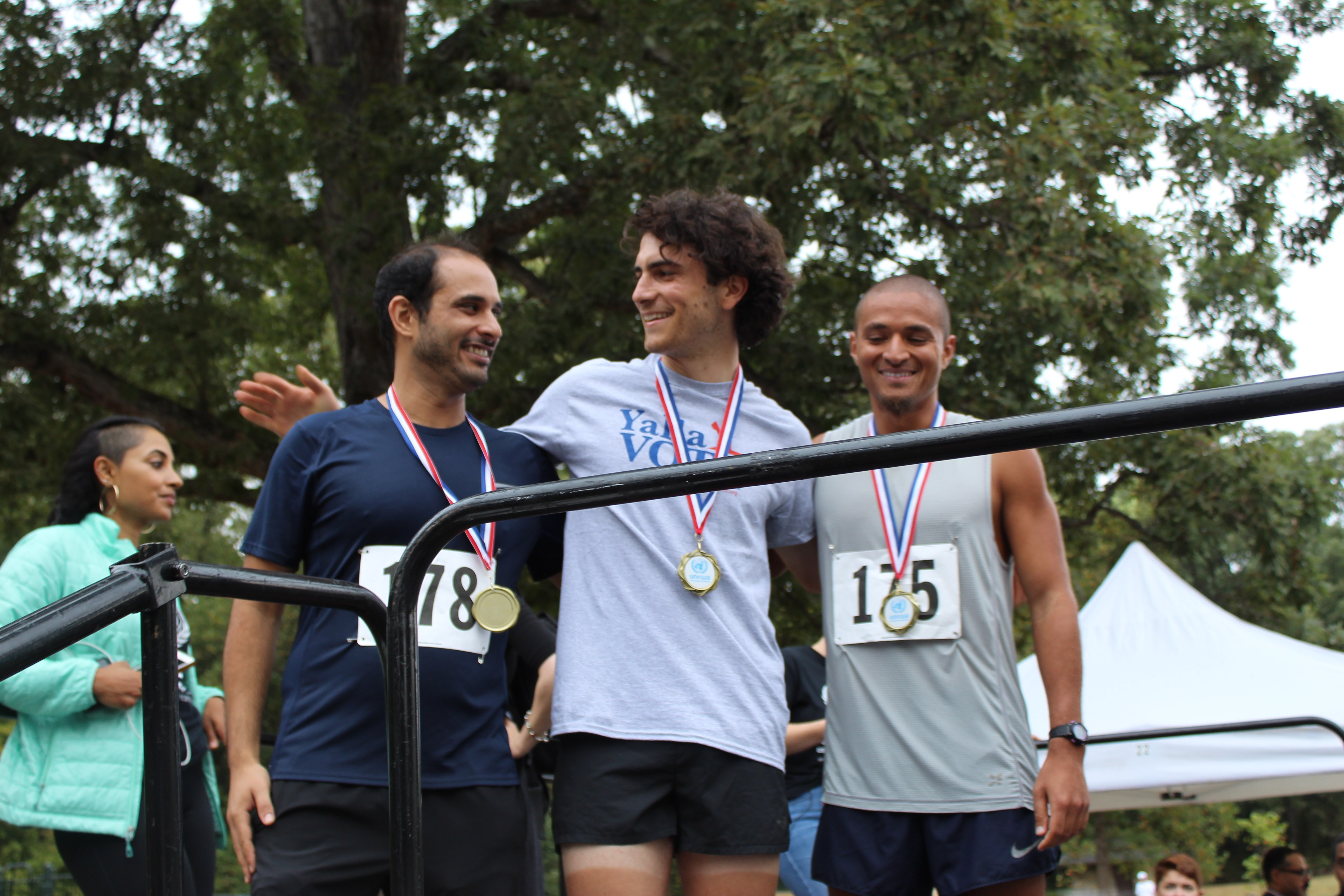 Kai Wiggins standing between two other runners after accepting their medals at the Gaza 5k (MEE/Sheren Khalel)