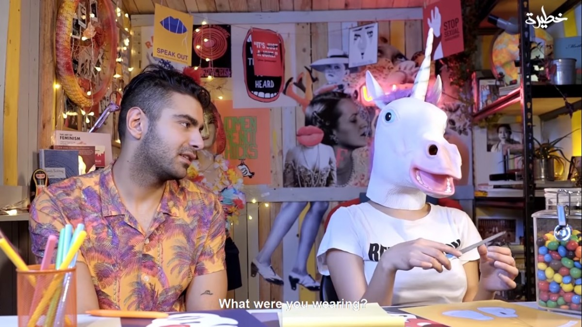 Maria, with a unicorn head, being questioned by her male co-presenter (screengrab)