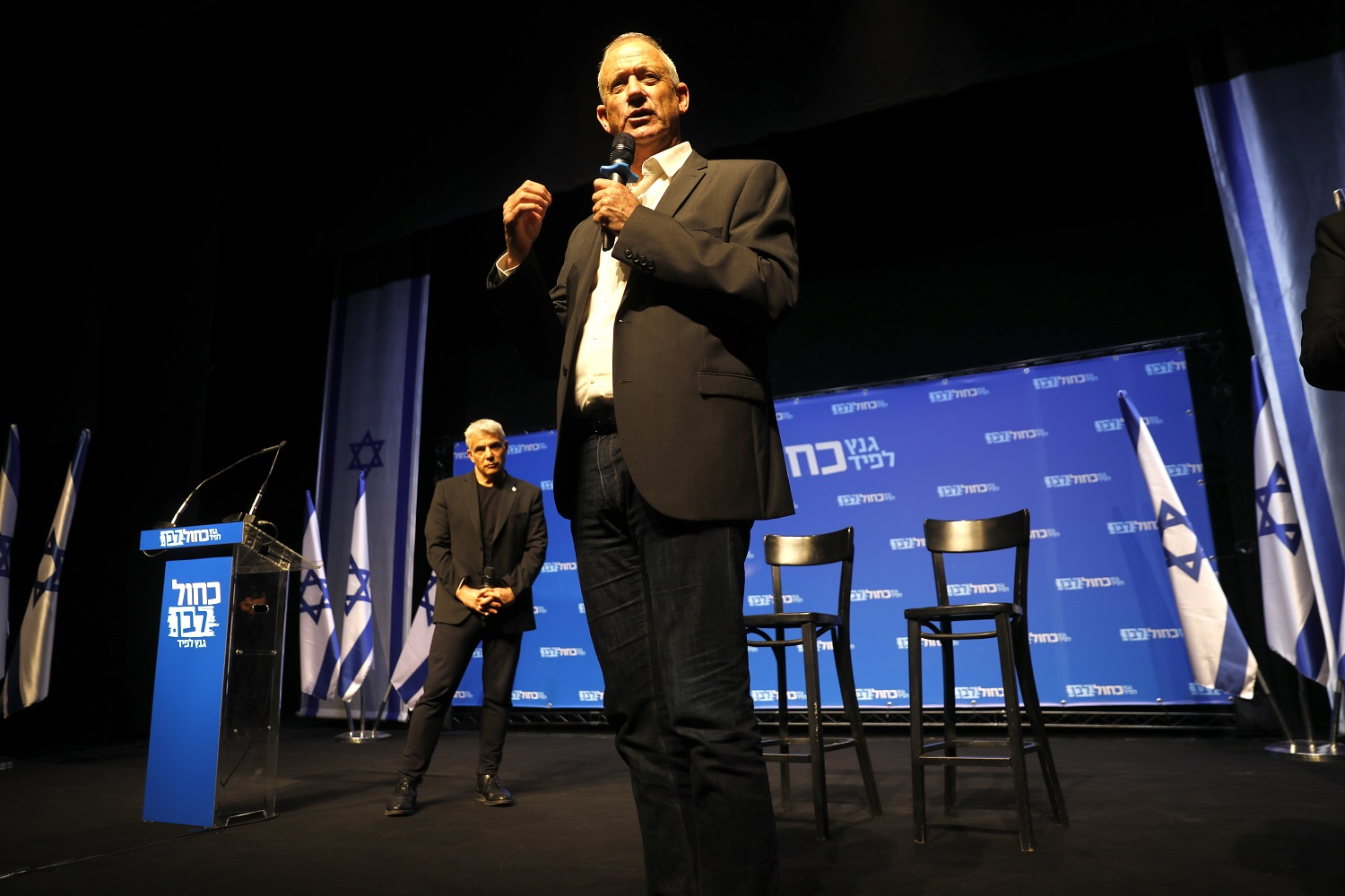 Yair Lapid (left) looks on during a speech by Benny Gantz in Beersheva in March 2019 (AFP)
