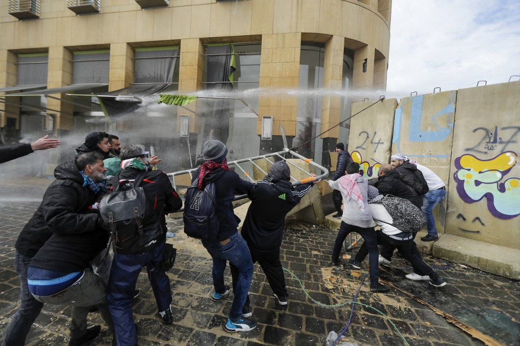 Anti-government protester pull on a section of the cement blocks protecting state institutions in central Beirut during protests on February 11, 2020