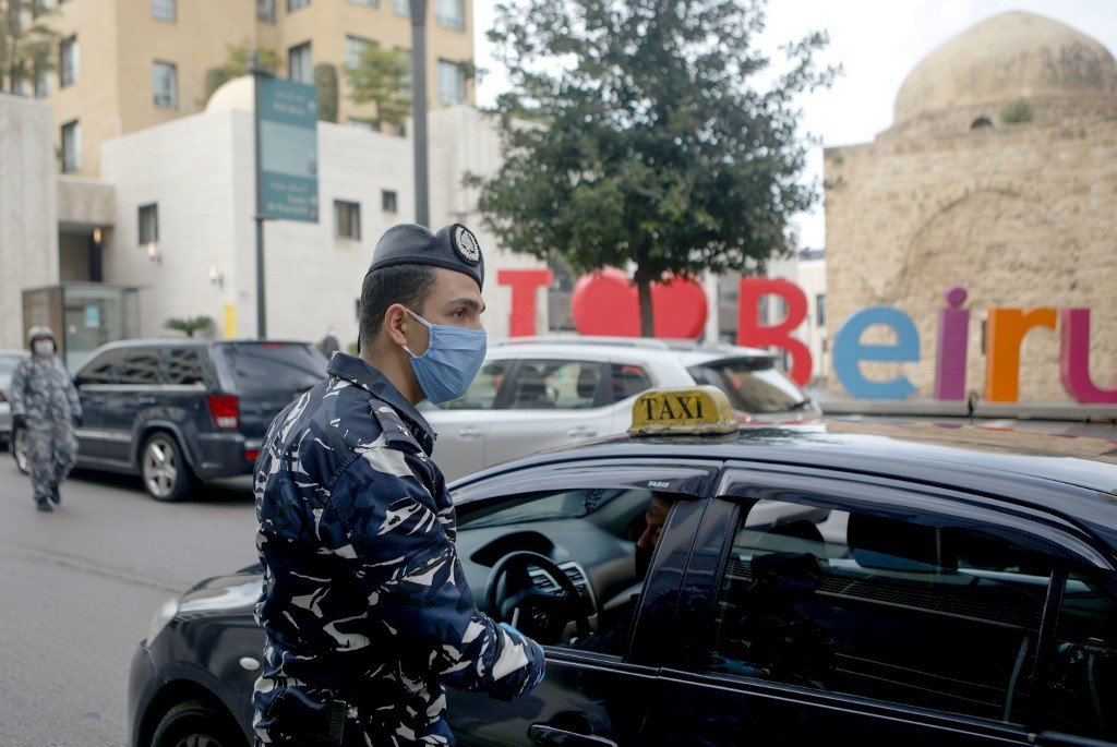 A Lebanese security officer mans a checkpoint to implement a coronavirus curfew in Beirut on 23 March (AFP)