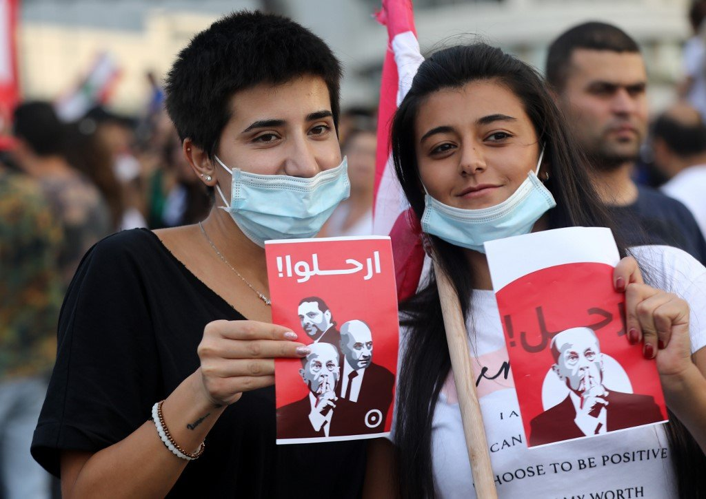 Protesters hold signs with the faces of Lebanese leaders and the word 'leave' on 18 October (AFP)